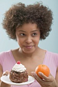 Young woman undecided between cake and orange
