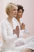 Two young women meditating