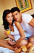 Couple sitting on bed eating breakfast