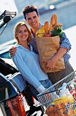 Couple food shopping with shopping trolley next to car