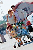 Couple with shopping trolley on supermarket car park