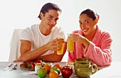 Couple eating breakfast of fruit and juice