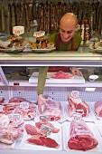 Butcher behind butcher's counter