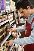 Man inserting price labels into supermarket shelves