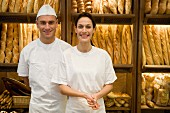 Baker and sales assistant in bakery with racks of baguettes