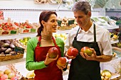 Two supermarket sales assistants with mangos