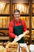 Bakery sales assistant packing baguette in bag
