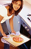 Woman taking pizza out of oven