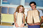 Couple in kitchen with paper bags of shopping