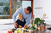 Father and son chopping vegetables in kitchen