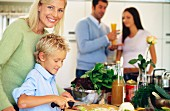Mother chopping vegetables with son in kitchen