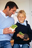 Father and son holding vegetables