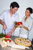 Couple topping a pizza in kitchen