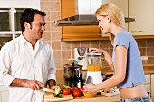 Man and woman making vegetable puree in kitchen