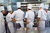 Chefs talking amongst themselves in a commercial kitchen