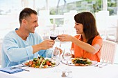 Couple on holiday clinking wine glasses over lunch