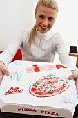 Blonde woman holding pizza box
