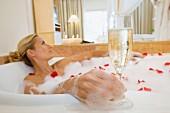 Frau mit Glas Sekt in Badewanne nimmt Rosenblütenblätter-Bad