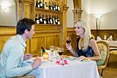 Pärchen in einem Restaurant beim Abendessen mit Wein