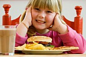 Girl sitting in front of plate of hamburger and crisps
