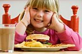 Mädchen sitzt vor Teller mit Hamburger und Chips