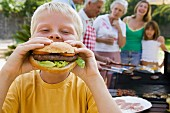 Boy biting into whole home-made burger