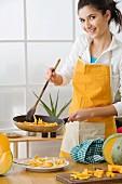 Woman in apron frying pumpkin in pan