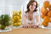 Woman sitting at table behind jars full of citrus fruits