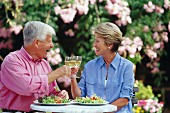 Older married couple clinking glasses of white wine