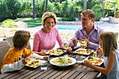 Family eating lunch of salad and pasta on holiday