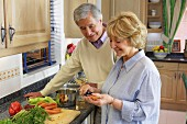 Older couple chopping vegetables in kitchen