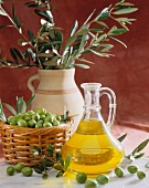 Olive oil with freshly harvested green olives in front of olive branches