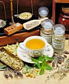 Assorted medicinal herbs, a set of precision scales and a cup of camomile tea