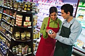 Two shop assistants in front of supermarket shelf
