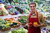 Shop assistant in front of vegetable racks