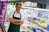 Shop assistant in front of chiller cabinets of dairy products