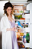 Woman in front of open refrigerator pouring a glass of milk