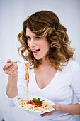 Young woman eating spaghetti with fork, portrait