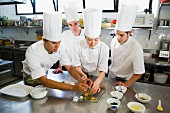 Chefs in a commercial kitchen preparing a dish