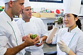A head chef explaining to a trainee how to check that an artichoke is fresh
