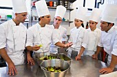 Chefs and trainee chefs learning about food in a commercial kitchen