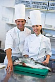 Two chefs with a salmon