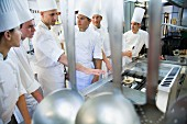 A head chef and trainee chefs in a commercial kitchen