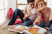 Couple eating pizza out of pizza box