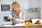 Woman in kitchen with shopping calculating household budget
