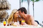 Paar macht Urlaub am Strand mit Cocktails