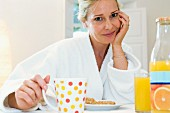 Woman eating breakfast in dressing gown