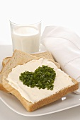 Soft cheese on toast with chives in heart shape, glass of milk