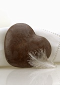 Brown heart-shaped stone and a feather