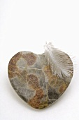Heart-shaped stone and a feather
